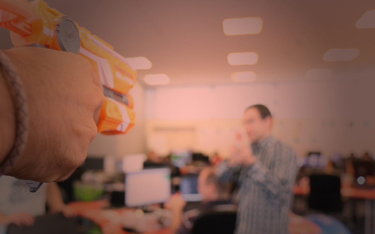 two people holding a toy gun at each other, playing in the office