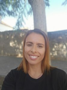 Petra Palma, part of e.near's Human Resource Team as one of the Talent Management Specialists. She is wearing an e.near t-shirt and smiling at the camera