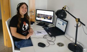 Maria João, part of e.near's Human Resource Team as one of the Talent Management Specialists, sitted by two screens, working at home. She is wearing an e.near t-shirt and smiling at the camera